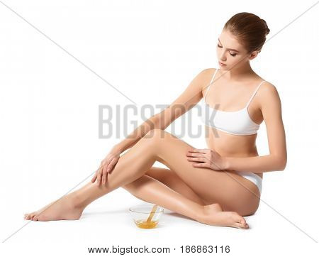 Beautiful young woman with sugaring paste on white background