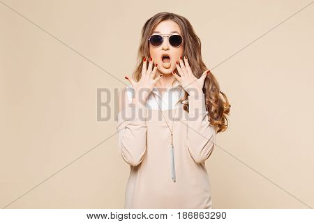 Studio portrait of beautiful shocked emotionally woman surprising looking at camera with opened mouth, touching face by hands and screaming. Stylish girl in beige dress, wavy hair, perfect manicure.