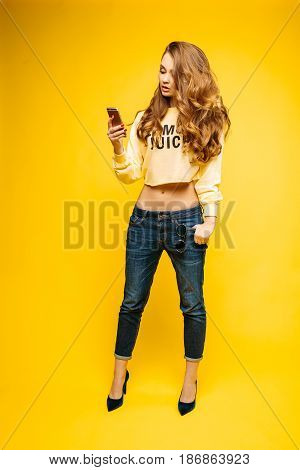Fashionable and sexy brunette wearing in crop sweatshirt, jeans and heels, posing at studio against yellow background and using call phone. Stylish beautiful woman taking photo, writing message at smart phone.