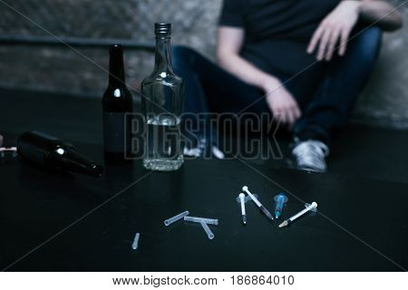 Different ways of creating parallel world. Different full big bottles located on the table in the garage next to the used syringes while junkie sitting in the background