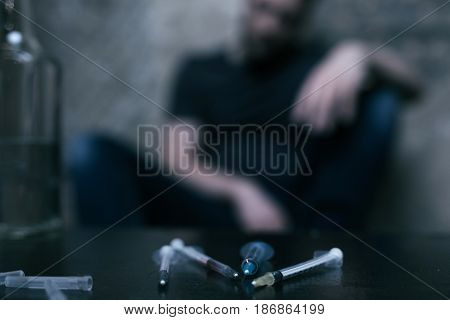 Tools of drug obsessed man . Different used medical syringes lying on the table while junkie sitting in the background