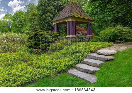 Rock stone stair steps leading up to gazebo in backyard garden