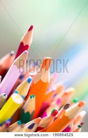 Stack of different color used wooden pencil with orange color stand out on a bright green background as diversity concept