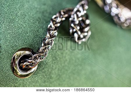 Shiny chrome metal rivet and steel chain in beautiful green leather fabric surface as fashion design and material background concept