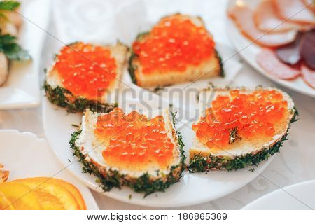 Sandwich with red caviar. Butter black bread and red caviar