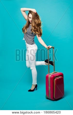 Pretty and stylish brunette woman posing with travel bag, touching wavy hair, holding leg up and looking down.Fashionable girl in white jeans and striped blouse after airport. Prepparing for vacation.