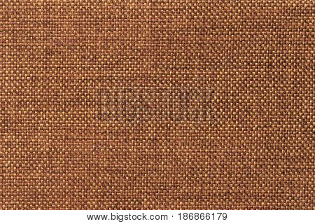 Dark orange woolen background of dense woven bagging fabric closeup. Structure of the ginger cloth with natural texture. Cloth backdrop.
