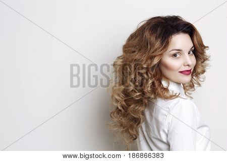 Side view of curly woman with long hair and stylish volume haircut turned away but looking at camera. Smiling girl with red lips after beauty salon posing at studio.