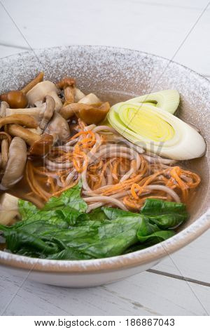 Soba buckwheat noodles soup with mushrooms and vegetables