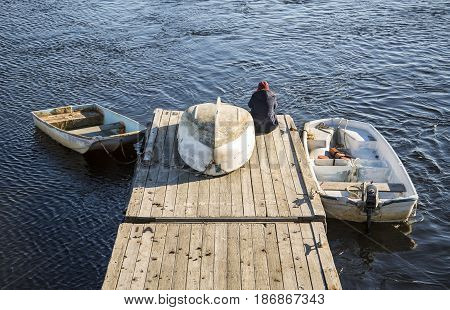 boats and a person on the ocean pier in Maine, USA