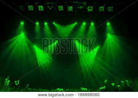 The green light from the spotlights through the smoke in the theatre during the performance. Lighting equipment.