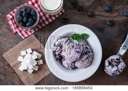 Blueberry homemade ice cream with mint leaves and Spoon for ice cream on stone slate background. Ingredients for ice cream