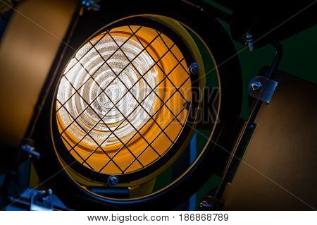 Fresnel lens, barn doors, protective metal mesh. Spotlight with directional light. Halogen lamps. Close-up.