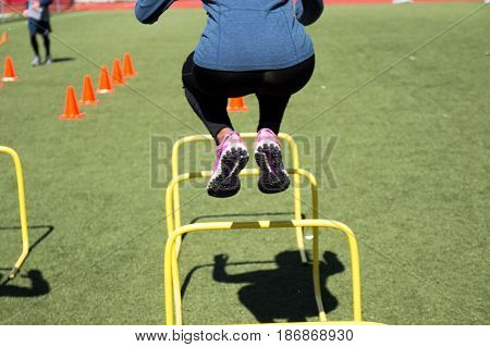 A track and field athlete doing agility training by jumping over yellow hurdles on a green turf field