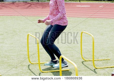 An athlete lands between yellow hurdles getting ready to jump over the next