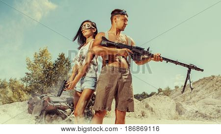 Sexy Couple Of Bikers With The Guns On The Desert Background.