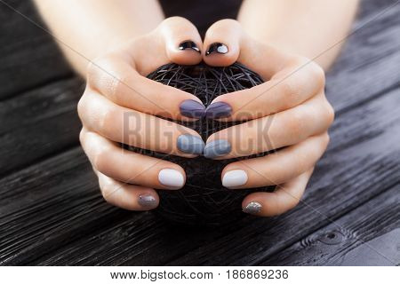 gray manicure with a black ball of yarn on the black wooden table.
