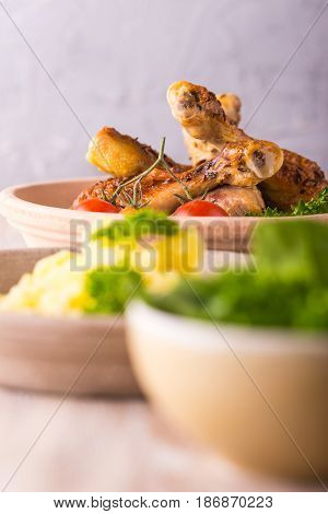 Portion Of Chicken Legs On Plate Behind Potatoes And Salad