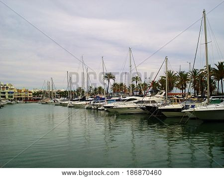 Puerto Marina is beautiful unusual stylish harbor with pier for yachts and a huge entertainment complex with a set of shops and cafe. The number of parking spaces for yachts is equal 1100. On the photo boats at pier are represented