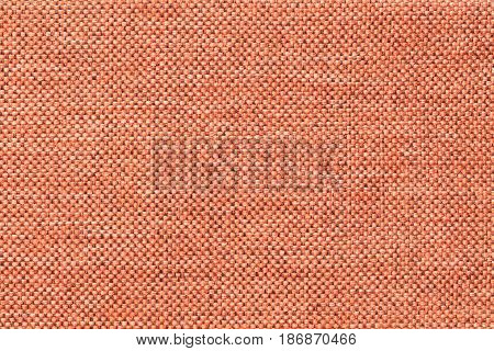 Bright orange woolen background of dense woven bagging fabric closeup. Structure of the coral cloth with natural texture. Cloth backdrop.