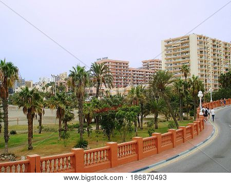 View of a resort city with buildings of hotels and beach is represented on the photo The walking path passes across the roadside which is laid out by a red tile and a low fence