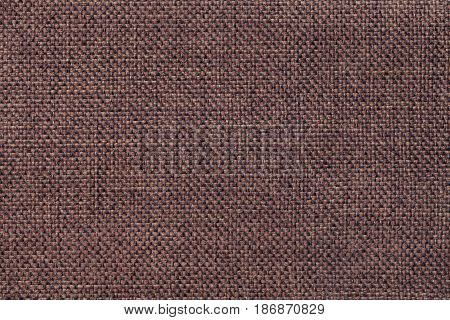 Dark brown background of dense woven bagging fabric closeup. Structure of the umber cloth with natural texture. Cloth backdrop.