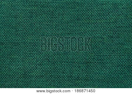 Dark green shiny background of dense woven bagging fabric closeup. Structure of the emerald cloth with natural texture. Cloth backdrop.