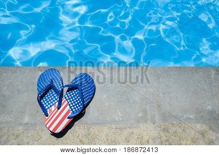 Summer background with heart of flip flops with American flag colors and pattern near the swimming pool