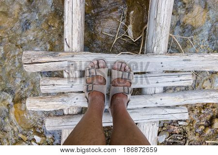 A fragment of a wooden deck across the river. Dirty feet in sandals. View from above.