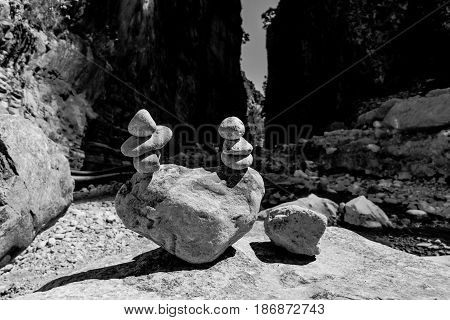 Samaria Gorge. Tourist tradition - a way of stones in the form of slides in series or in the form of a pyramid. Island of Crete Greece. Black and white.