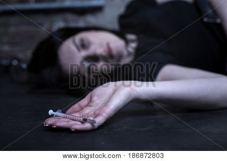 Waiting for my death. Obsessed homeless tired woman lying in the dark place and holding empty syringe while expressing apathy
