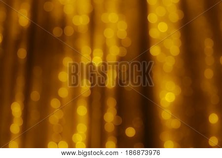 Abstract gold blurred background. The lights of illuminations or lights in a blur. Bokeh and defocusing