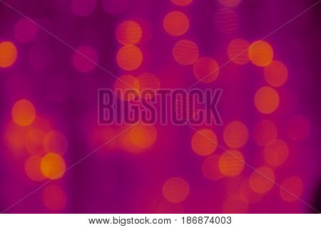 Yellow and purple abstract blurred background. Festive garland in blur, bokeh. Colored lights in blur