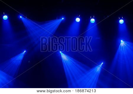 Lighting equipment on the stage. Blue rays of light through the smoke during theatrical performances.