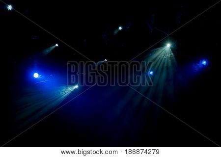 Blue rays of light through the smoke on stage. Theater performance. Lighting equipment
