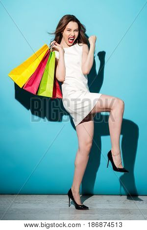 Portrait of a happy satisfied woman holding shopping bags and celebrating isolated over blue background
