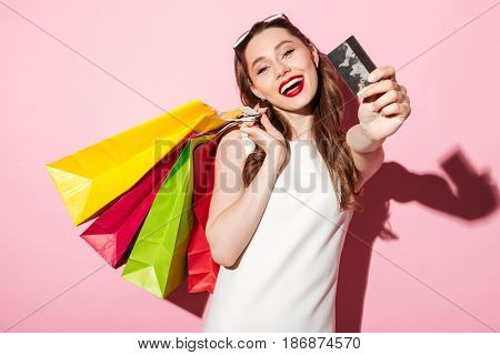 Image of a happy young brunette woman in white summer dress holding credit card posing with shopping bags and looking at camera over pink background.