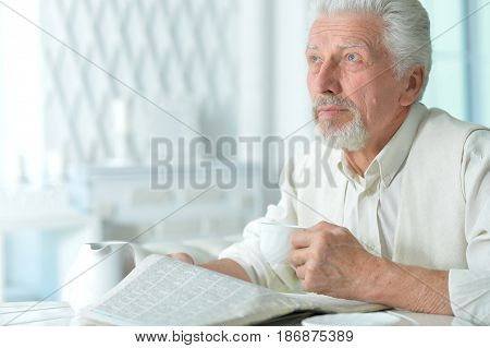 Portrait of an elderly man reading a newspaper
