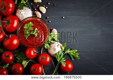 Still life with fresh tomatoes, garlic, parsley, tomato sauce and pepper on black wooden boards.