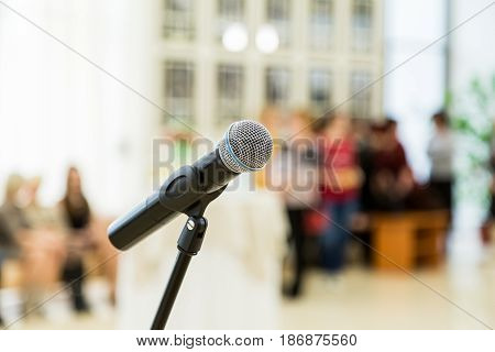 Wireless microphone on the stand at a reception in the hall. People in the background. Blurred background. Bokeh.