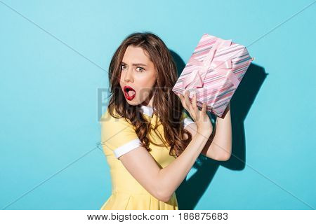 Portrait of an astonished pretty girl in dress holding gift box isolated over blue background