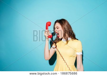 Portrait of an angry furious girl in dress screaming at retro telephone tube isolated over blue background