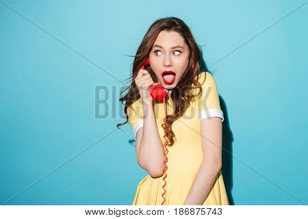 Portrait of a shocked young girl in dress talking on retro telephone tube and looking away at copyspace isolated over blue background