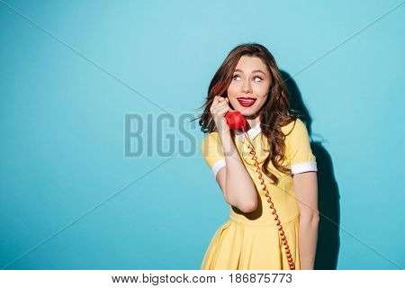 Portrait of an attractive young girl in dress talking on retro telephone tube and looking away at copyspace isolated over blue background