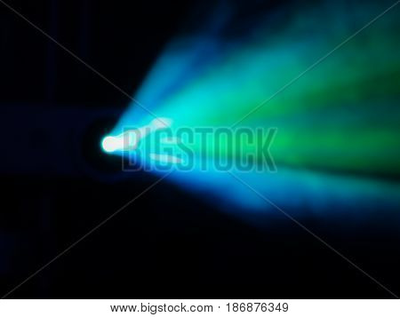 Blue-green rays of light through the smoke from the projector. Lighting equipment. Show, performance, concert or night club. The image is not in focus. Bokeh
