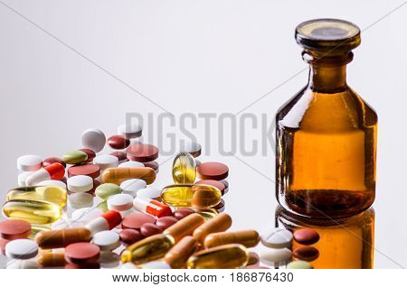 colored pills with a small brown bottle of glas - selected focus; narrow depth of field