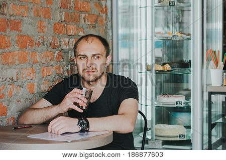 Gorgeous man. Vertical portrait of a handsome young elegant man in a suit having a drink looking away with interest