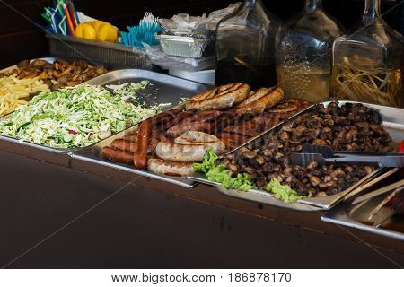 Delicious Sausages Bbq Vegetables Grilling On Open Grill, Outdoor Kitchen. Food Festival In City. Ta