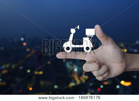 Motor bike icon on finger over blur colorful night light city tower Business delivery service concept