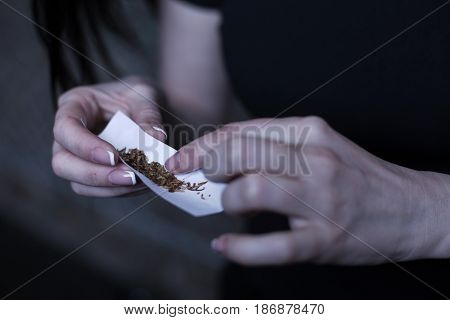 Using illegal drugs. Skillful young marijuana addicted woman holding marijuana cigarette while getting new drug dose and applying skills